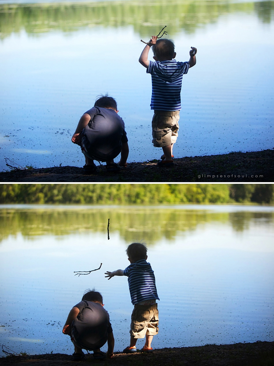 boys throwing sticks in lake